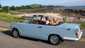 Triumph Herad Convertible by a beach | Best things to do in Dumfries and Galloway | Kippford Classic Car Hire